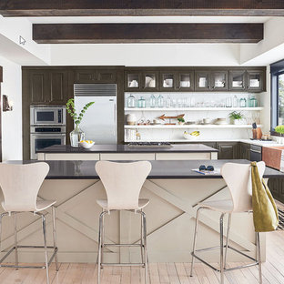 Design ideas for a large modern l-shaped eat-in kitchen in Houston with a double-bowl sink, raised-panel cabinets, dark wood cabinets, quartz benchtops, white splashback, marble splashback, stainless steel appliances, light hardwood floors, multiple islands, pink floor and black benchtop.