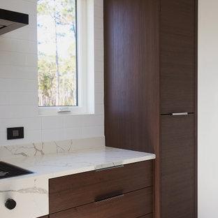 マイアミの中くらいのモダンスタイルのおしゃれなキッチン (ドロップインシンク、フラットパネル扉のキャビネット、茶色いキャビネット、珪岩カウンター、白いキッチンパネル、セラミックタイルのキッチンパネル、シルバーの調理設備、大理石の床、白い床、白いキッチンカウンター) の写真