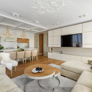 Неиссякаемый источник вдохновения для домашнего уюта: открытая гостиная комната в современном стиле с бежевыми стенами, паркетным полом среднего тона, коричневым полом и телевизором на стене