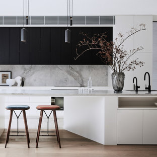 Inspiration for a large contemporary l-shaped open plan kitchen in Sydney with a double-bowl sink, flat-panel cabinets, white cabinets, marble benchtops, grey splashback, marble splashback, black appliances, medium hardwood floors, with island, brown floor and grey benchtop.