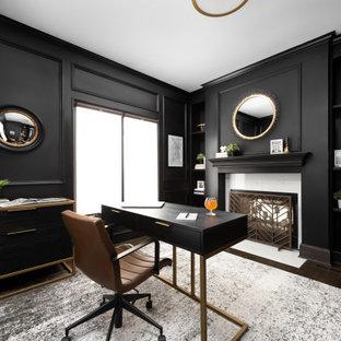 Foto de despacho boiserie, tradicional renovado, grande, boiserie, con paredes negras, suelo de madera oscura, chimenea de doble cara, marco de chimenea de piedra, escritorio independiente y boiserie