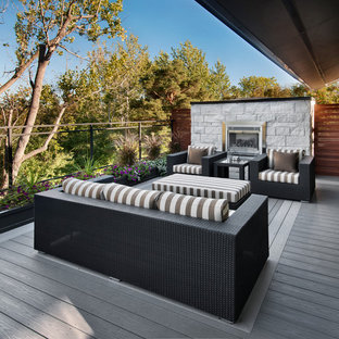 Inspiration for a mid-sized contemporary deck remodel in Ottawa with a fire pit and a roof extension