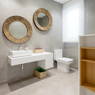 Esempio di un bagno di servizio contemporaneo di medie dimensioni con WC a due pezzi, pareti grigie, pavimento con piastrelle in ceramica, ante lisce, ante bianche, lavabo a bacinella e pavimento beige