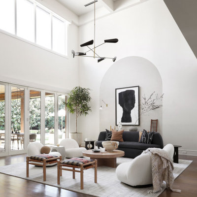 Example of a large trendy open concept medium tone wood floor and vaulted ceiling living room design in Dallas with white walls and a concealed tv