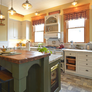 Photo of a small traditional l-shaped separate kitchen in San Luis Obispo with a farmhouse sink, raised-panel cabinets, green cabinets, quartzite benchtops, white splashback, subway tile splashback, panelled appliances, brick floors, with island, grey floor and white benchtop.