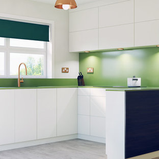 Photo of a mid-sized contemporary u-shaped eat-in kitchen in Cambridgeshire with flat-panel cabinets, white cabinets, solid surface benchtops, green splashback, no island and green benchtop.