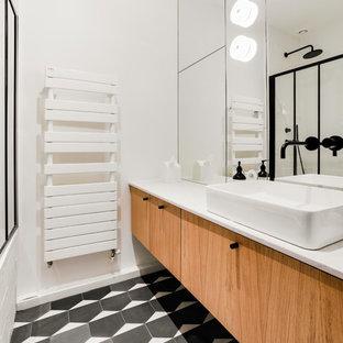 パリの中サイズのコンテンポラリースタイルのおしゃれなマスターバスルーム (フラットパネル扉のキャビネット、淡色木目調キャビネット、アンダーマウント型浴槽、シャワー付き浴槽、白いタイル、テラコッタタイル、白い壁、セメントタイルの床、ベッセル式洗面器、珪岩の洗面台、黒い床、開き戸のシャワー、ベージュのカウンター) の写真