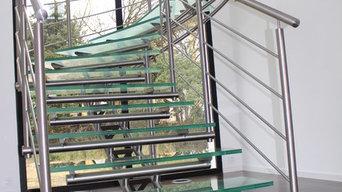 Escalier demi tournant à limon central tridimensionel et marche en verre