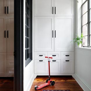 Ispirazione per un armadio incassato unisex boho chic di medie dimensioni con ante in stile shaker, ante in legno scuro, pavimento in legno massello medio e pavimento marrone