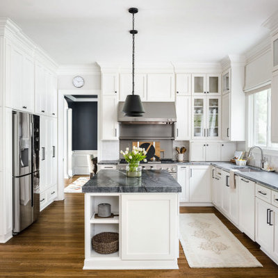 Example of a mid-sized transitional l-shaped medium tone wood floor and brown floor eat-in kitchen design in Charlotte with an undermount sink, shaker cabinets, white cabinets, quartzite countertops, gray backsplash, porcelain backsplash, stainless steel appliances, an island and black countertops