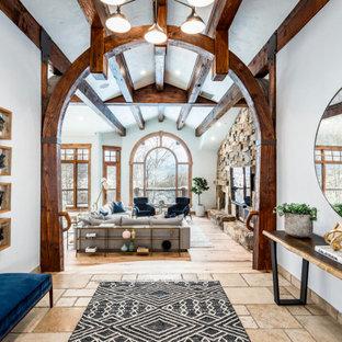 Inspiration för en stor rustik hall, med vita väggar, kalkstensgolv och beiget golv