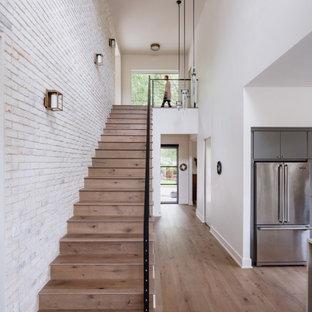 Idée de décoration pour un petit escalier droit design avec des marches en bois, des contremarches en bois, un garde-corps en métal et un mur en parement de brique.