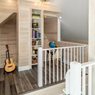 На фото: нейтральная детская в морском стиле с рабочим местом, серыми стенами, темным паркетным полом, коричневым полом и деревянными стенами с