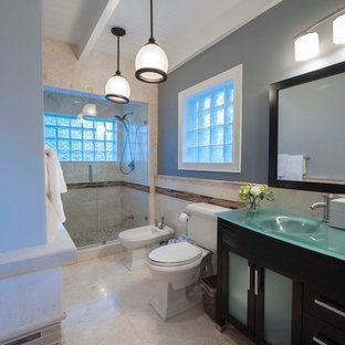 Idee per una stanza da bagno padronale stile marinaro di medie dimensioni con lavabo integrato, ante lisce, ante nere, top in vetro, doccia alcova, WC a due pezzi, piastrelle beige, piastrelle in pietra, pareti grigie e pavimento in marmo