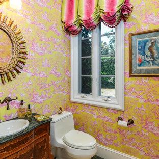 Идея дизайна: туалет среднего размера в викторианском стиле с фасадами островного типа, темными деревянными фасадами, унитазом-моноблоком, желтыми стенами, накладной раковиной, зеленым полом, зеленой столешницей и напольной тумбой