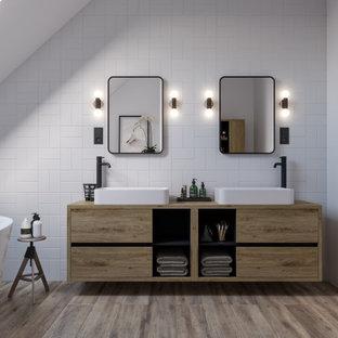 Modern inredning av ett mellanstort brun brunt badrum för barn, med släta luckor, bruna skåp, ett fristående badkar, en vägghängd toalettstol, vit kakel, keramikplattor, vita väggar, klinkergolv i keramik, ett konsol handfat, laminatbänkskiva och brunt golv