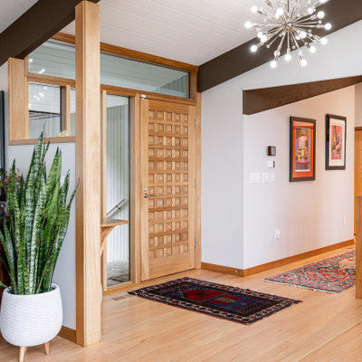 Inspiration for a mid-sized mid-century modern light wood floor, beige floor and exposed beam entryway remodel in Other with gray walls and a light wood front door