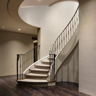 Klassisk inredning av en stor svängd trappa i trä, med sättsteg med heltäckningsmatta och räcke i metall