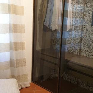 Esempio di uno spazio per vestirsi unisex moderno di medie dimensioni con ante di vetro, ante marroni, pavimento in mattoni e pavimento marrone