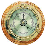 """Precision Brass Porthole Barometer - The precision brass porthole barometer measures 9.5""""Dia x 2""""D. This german precision barometer comes in a solid brass tarnish proof case with beveled glass and an oak wood base. It's movements are calibrated for altitudes to 3500' above sea level. It will add a definite nautical touch to whatever room it is placed in and is a must have for those who appreciate high quality nautical decor. It will accurately and precisely predict weather conditions coming to your area."""