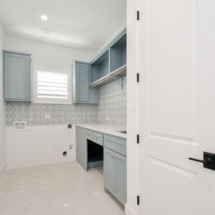 Klassisk inredning av en stor vita linjär vitt tvättstuga enbart för tvätt, med en undermonterad diskho, skåp i shakerstil, turkosa skåp, bänkskiva i kvarts, flerfärgad stänkskydd, stänkskydd i porslinskakel, vita väggar, klinkergolv i porslin, en tvättmaskin och torktumlare bredvid varandra och beiget golv