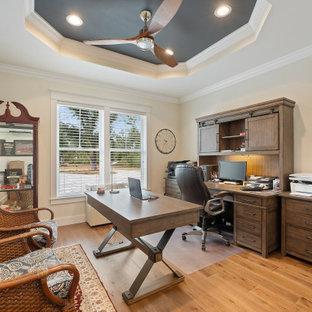 Großes Country Arbeitszimmer mit Arbeitsplatz, beiger Wandfarbe, braunem Holzboden, freistehendem Schreibtisch, braunem Boden und eingelassener Decke in Sonstige