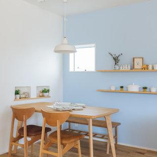Immagine di una piccola sala da pranzo aperta verso il soggiorno scandinava con pareti blu, parquet chiaro, pavimento beige, soffitto in carta da parati e carta da parati
