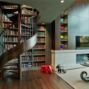 ナッシュビルの広いコンテンポラリースタイルのおしゃれなホームオフィス・書斎 (ライブラリー、茶色い壁、濃色無垢フローリング、横長型暖炉、石材の暖炉まわり、自立型机、茶色い床、板張り天井、板張り壁) の写真