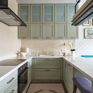Свежая идея для дизайна: маленькая п-образная кухня-гостиная в стиле современная классика с накладной раковиной, столешницей из кварцевого композита, бежевым фартуком, фартуком из плитки кабанчик, черной техникой, паркетным полом среднего тона, полуостровом, фасадами с утопленной филенкой, зелеными фасадами и бежевым полом - отличное фото интерьера