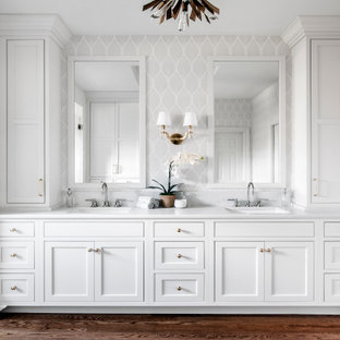 Example of a large classic master white tile and porcelain tile medium tone wood floor, brown floor, double-sink, tray ceiling and wallpaper bathroom design in Nashville with recessed-panel cabinets, white cabinets, a two-piece toilet, gray walls, an undermount sink, quartz countertops, a hinged shower door, white countertops, a niche and a built-in vanity