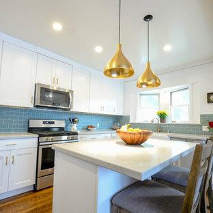 На фото: большая п-образная кухня-гостиная со шкафом над холодильником в современном стиле с раковиной в стиле кантри, фасадами в стиле шейкер, белыми фасадами, столешницей из кварцевого агломерата, синим фартуком, фартуком из плитки кабанчик, техникой из нержавеющей стали, паркетным полом среднего тона, островом, коричневым полом, серой столешницей и правильным освещением