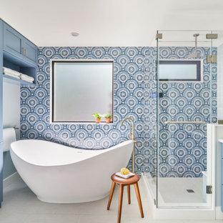 Свежая идея для дизайна: главная ванная комната среднего размера в стиле неоклассика (современная классика) с фасадами в стиле шейкер, синими фасадами, отдельно стоящей ванной, угловым душем, синей плиткой, стеклянной плиткой, синими стенами, врезной раковиной, душем с распашными дверями, белой столешницей, сиденьем для душа, тумбой под две раковины и встроенной тумбой - отличное фото интерьера