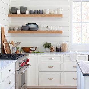 リッチモンドの広いカントリー風おしゃれなアイランドキッチン (エプロンフロントシンク、落し込みパネル扉のキャビネット、白いキャビネット、白いキッチンパネル、塗装板のキッチンパネル、シルバーの調理設備、淡色無垢フローリング、ベージュの床、グレーのキッチンカウンター、三角天井、大理石カウンター) の写真