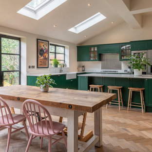 Photo of a large classic l-shaped open plan kitchen in London with a belfast sink, shaker cabinets, green cabinets, quartz worktops, metallic splashback, integrated appliances, medium hardwood flooring, an island and white worktops.