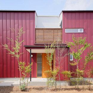 Réalisation d'une façade de maison rouge asiatique à un étage et de taille moyenne avec un toit à deux pans et un toit en métal.