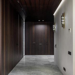 モスクワの中くらいのコンテンポラリースタイルのおしゃれな廊下 (茶色い壁、磁器タイルの床、グレーの床、板張り天井、羽目板の壁) の写真