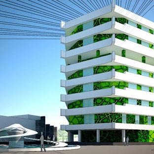 コンテンポラリースタイルのおしゃれな三階建ての家 (ガラスサイディング、緑の外壁、陸屋根、アパート・マンション) の写真