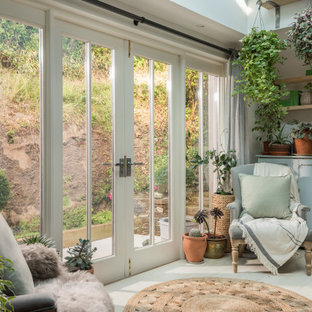 This is an example of a shabby-chic style conservatory in Cornwall with painted wood flooring, a skylight and white floors.