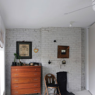 На фото: с высоким бюджетом маленькие хозяйские спальни в современном стиле с белыми стенами, деревянным полом, стандартным камином, фасадом камина из кирпича и белым полом