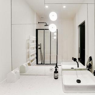 Imagen de cuarto de baño con ducha, actual, de tamaño medio, con armarios con paneles lisos, puertas de armario de madera clara, bañera encastrada sin remate, combinación de ducha y bañera, baldosas y/o azulejos blancos, baldosas y/o azulejos con efecto espejo, paredes blancas, suelo de azulejos de cemento, lavabo sobreencimera, encimera de cuarcita, suelo negro, ducha con puerta con bisagras y encimeras beige