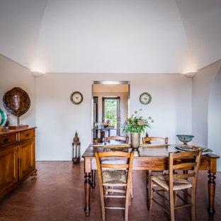 Idee per una sala da pranzo mediterranea con pareti grigie, pavimento in cemento, pavimento marrone e soffitto a volta