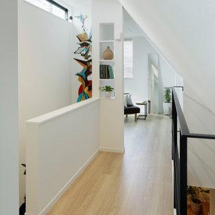 東京23区の中くらいの北欧スタイルのおしゃれな廊下 (白い壁、淡色無垢フローリング、ベージュの床、クロスの天井、壁紙、白い天井) の写真