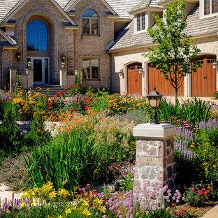 Ejemplo de acceso privado tradicional, grande, en verano, en patio delantero, con adoquines de piedra natural, muro de contención y exposición total al sol