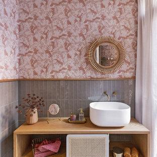 Imagen de cuarto de baño único, flotante y papel pintado, actual, papel pintado, con armarios abiertos, puertas de armario de madera oscura, baldosas y/o azulejos grises, paredes rosas, lavabo sobreencimera, suelo multicolor, encimeras marrones y papel pintado