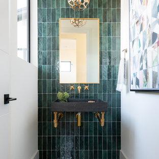 На фото: туалет в современном стиле с открытыми фасадами, серыми фасадами, зеленой плиткой, белыми стенами, подвесной раковиной, черным полом и подвесной тумбой
