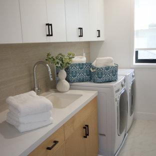 Bild på en stor funkis vita parallell vitt tvättstuga enbart för tvätt, med en undermonterad diskho, släta luckor, skåp i ljust trä, bänkskiva i kvarts, beige stänkskydd, beige väggar, marmorgolv, en tvättmaskin och torktumlare bredvid varandra och vitt golv