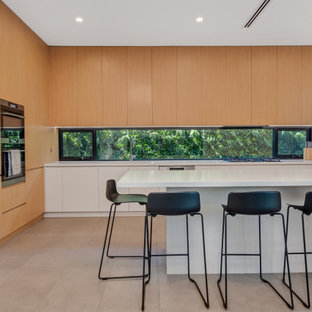 Photo of a contemporary galley kitchen in Sydney with an undermount sink, flat-panel cabinets, light wood cabinets, quartz benchtops and white benchtop.