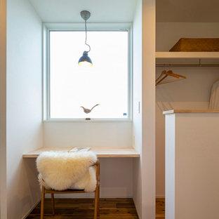 Mittelgroßes Nordisches Arbeitszimmer ohne Kamin mit Arbeitsplatz, weißer Wandfarbe, braunem Holzboden, Einbau-Schreibtisch, braunem Boden, Tapetendecke und Tapetenwänden in Sonstige