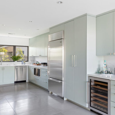 Kitchen - mid-century modern u-shaped gray floor kitchen idea in Orange County with an undermount sink, flat-panel cabinets, green cabinets, white backsplash, stainless steel appliances and white countertops