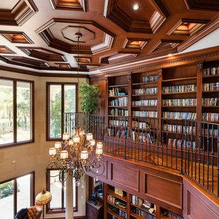 Foto di un ampio studio mediterraneo con libreria, pareti beige, pavimento in legno massello medio, camino classico, cornice del camino in pietra, scrivania autoportante e pavimento marrone